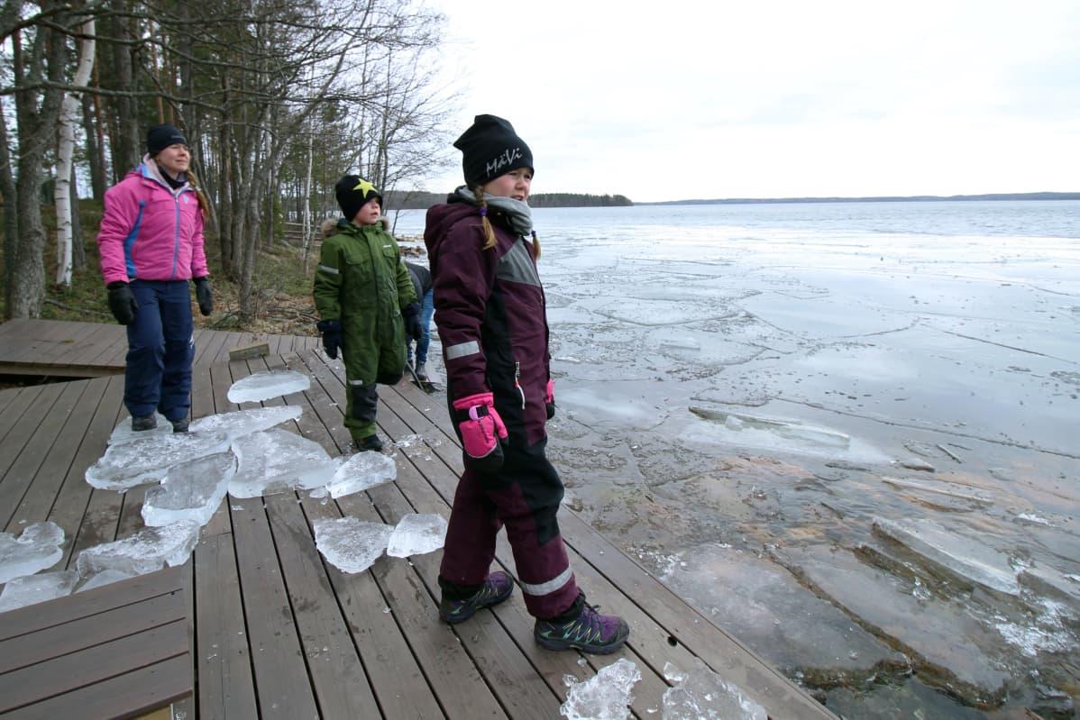 Perhe leikkii jääpaloilla järven rannassa.