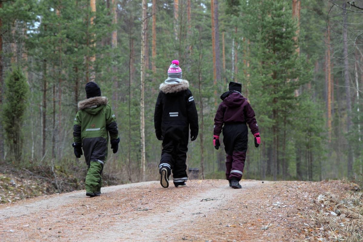 Lapsia metsässä kävelemässä.
