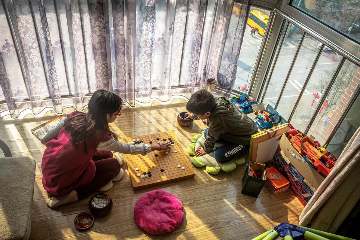 Lapset pelaavat lautapeliä kotonaan Pekingissä.