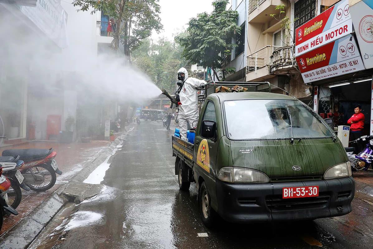 Sotilaat levittävät desinfiointiainetta kadulle lauantaina Vietnamin Hanoissa.