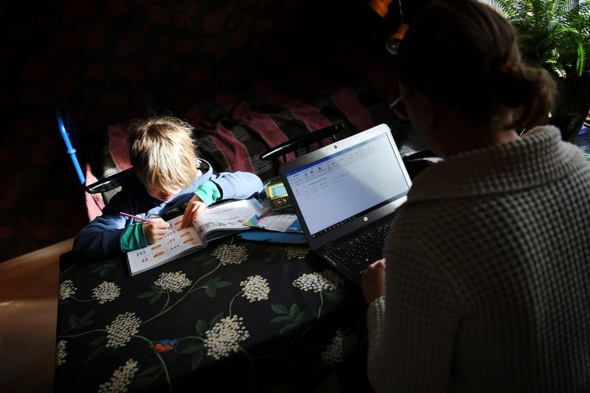 Koulusta kotiin jäänyt lapsi opiskelee yhdessä etätöitä tekevän äidin kanssa kotonaan Helsingissä tiistaina.