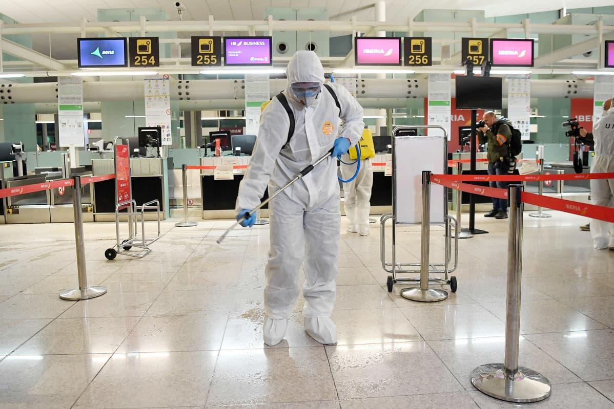 Suojapukuun pukeutunut työntekijä desinfioi lentoasemaa.