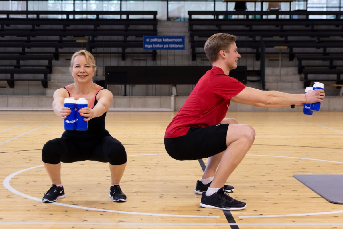 Ylen toimittaja Ulla Malminen kokeilee kotitreeniä Helsingin kaupungin liikunnanohjaajan Eero Kentän kanssa.