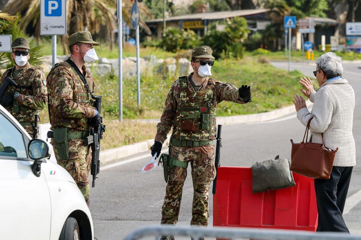 Nainen puhuu rajavalvontaa tekevien italialaisten sotilaiden kanssa.