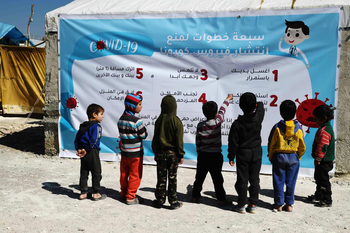 Syyrialaislapset tutkivat sunnuntaina 22. maaliskuuta pakolaisleirillä julistetta.
