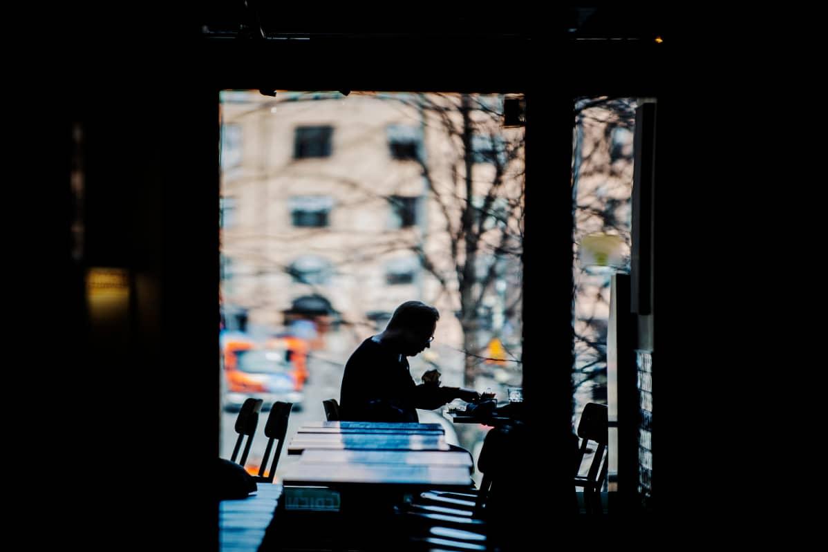 Mies syö lounasaikaan ravintolassa.