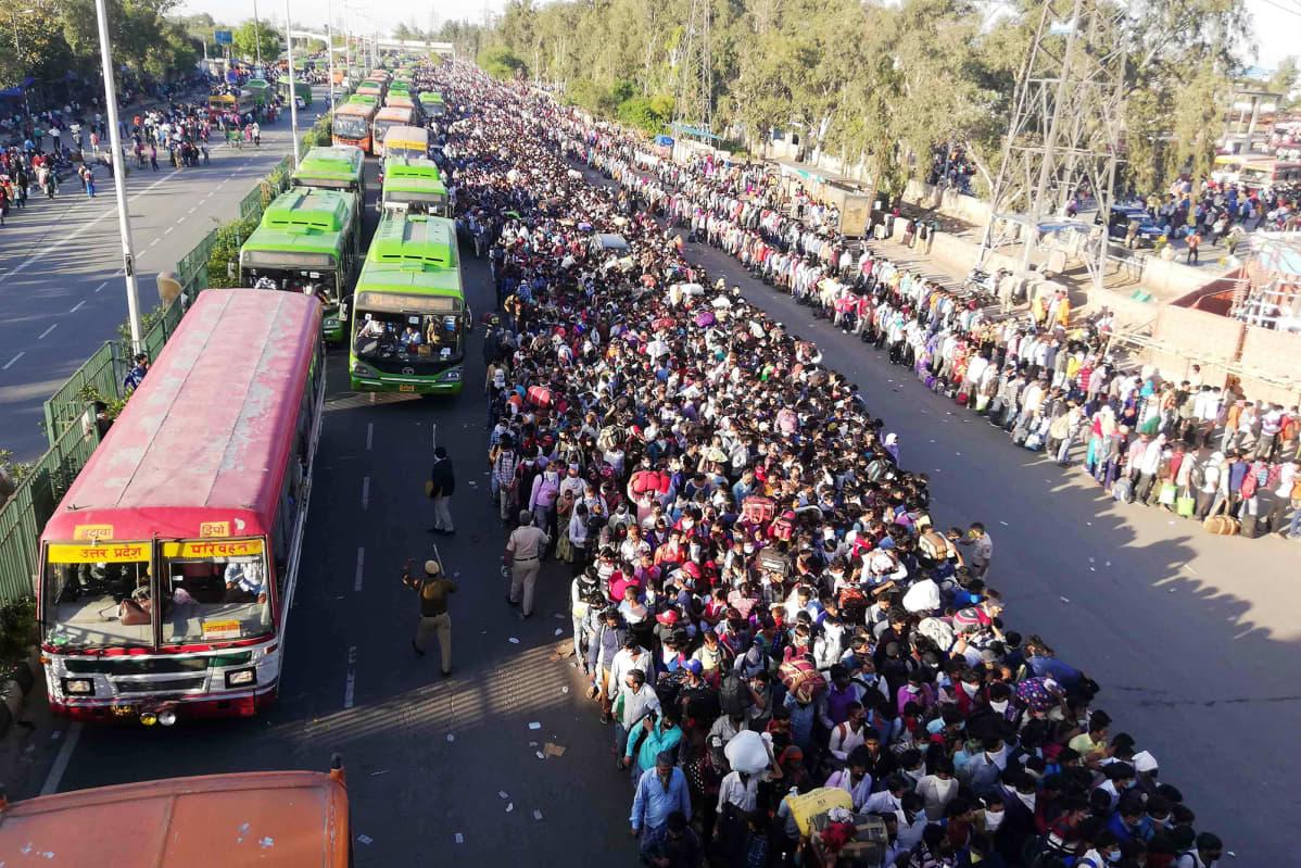 Tuhansittain ihmisiä jonottaa Anand Viharin bussiterminaalin ulkopuolella New Delhissä.
