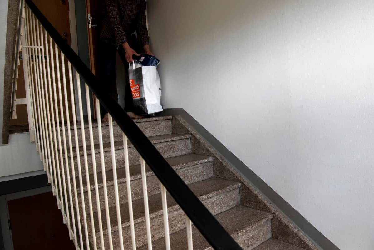 Mies nostaa kauppakassia ovensa ulkopuolelta kerrostalon rappukäytävässä.