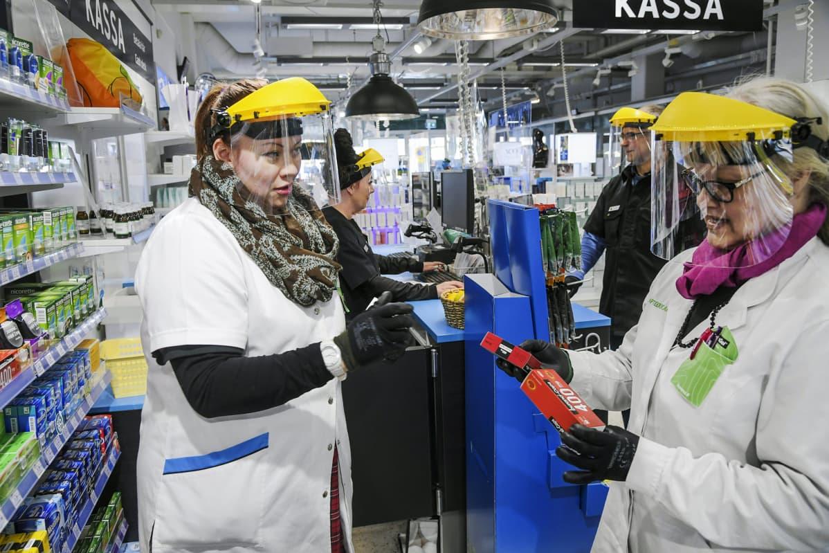 Apteekin työntekijät suojautuvat koronavirukselta suojavisiirillä varustetulla päähineellä sekä käyttämällä sormikkaita.