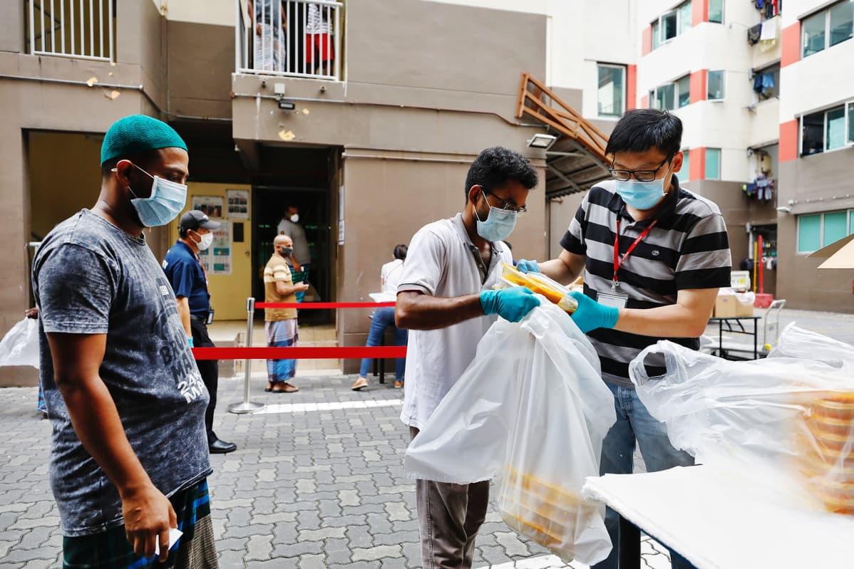 Ulkomaalaiset työntekijät keräävät aterioitaan pussiin mennäkseen karanteeniin.