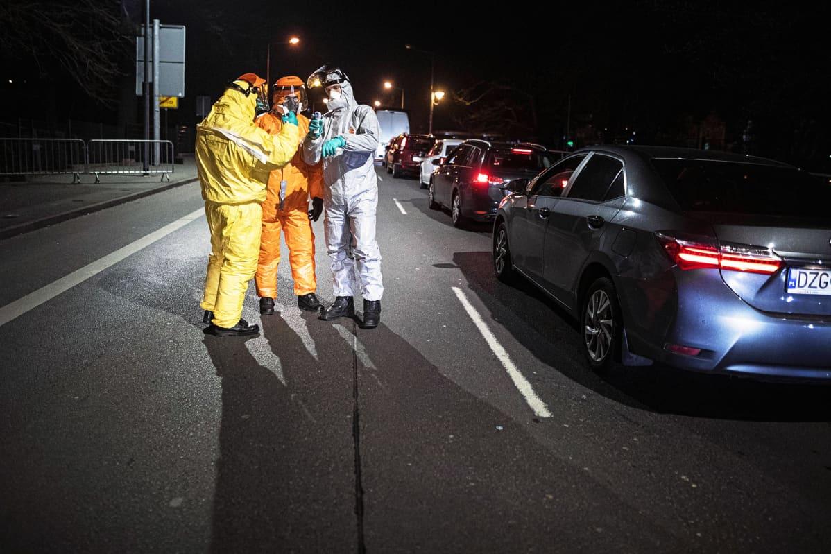 Suojavaatteisiin pukeutuneet tarkastajat mittaavat matkustajien ruumiinlämpöä Saksan ja Puolan rajalla Goerlitz.