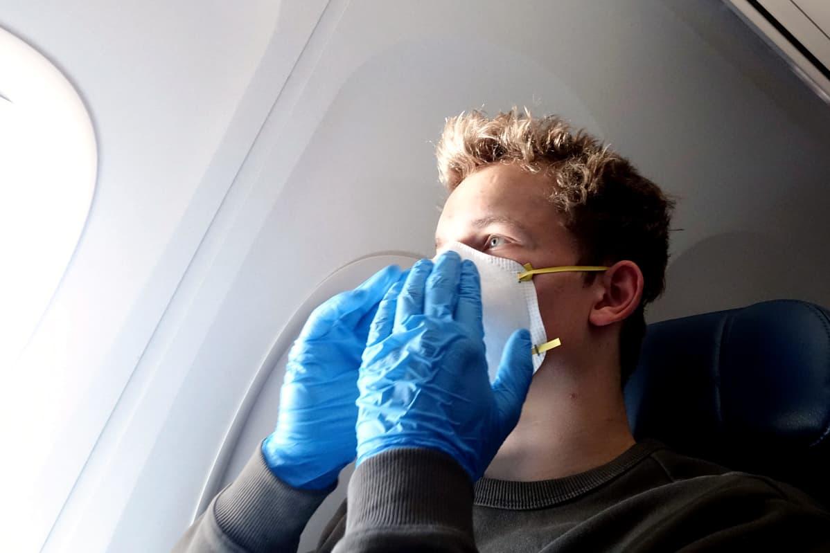 Hengityssuojaimeen ja suojakäsineisiin pukeutunut mies matkustaa lentokoneessa.