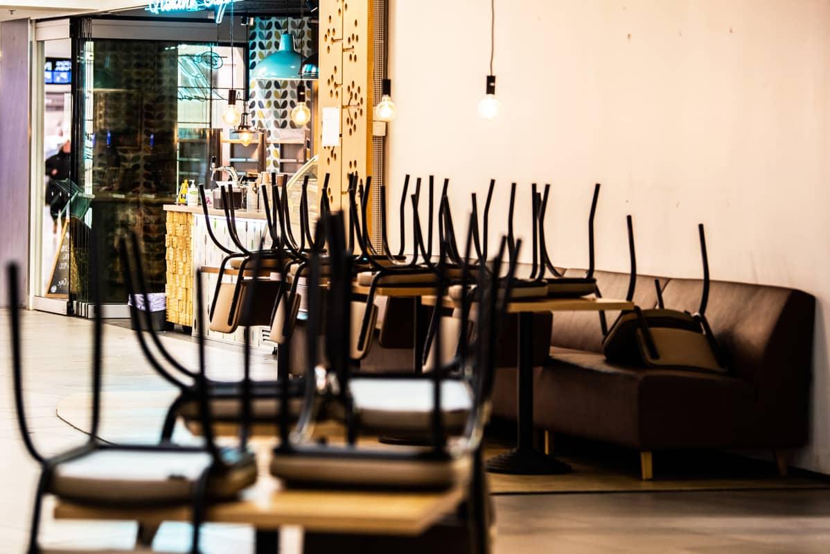 Pöydille nostettuja tuoleja tyhjässä ravintolassa kauppakeskuksessa.