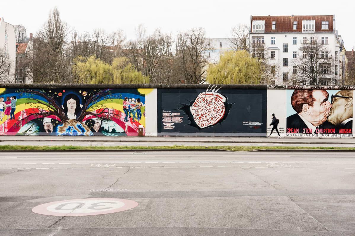 Jalankulkija autiolla jalkakäytävällä Berliinin East Side Galleryn edustalla. Koronakriisi vei turistit.