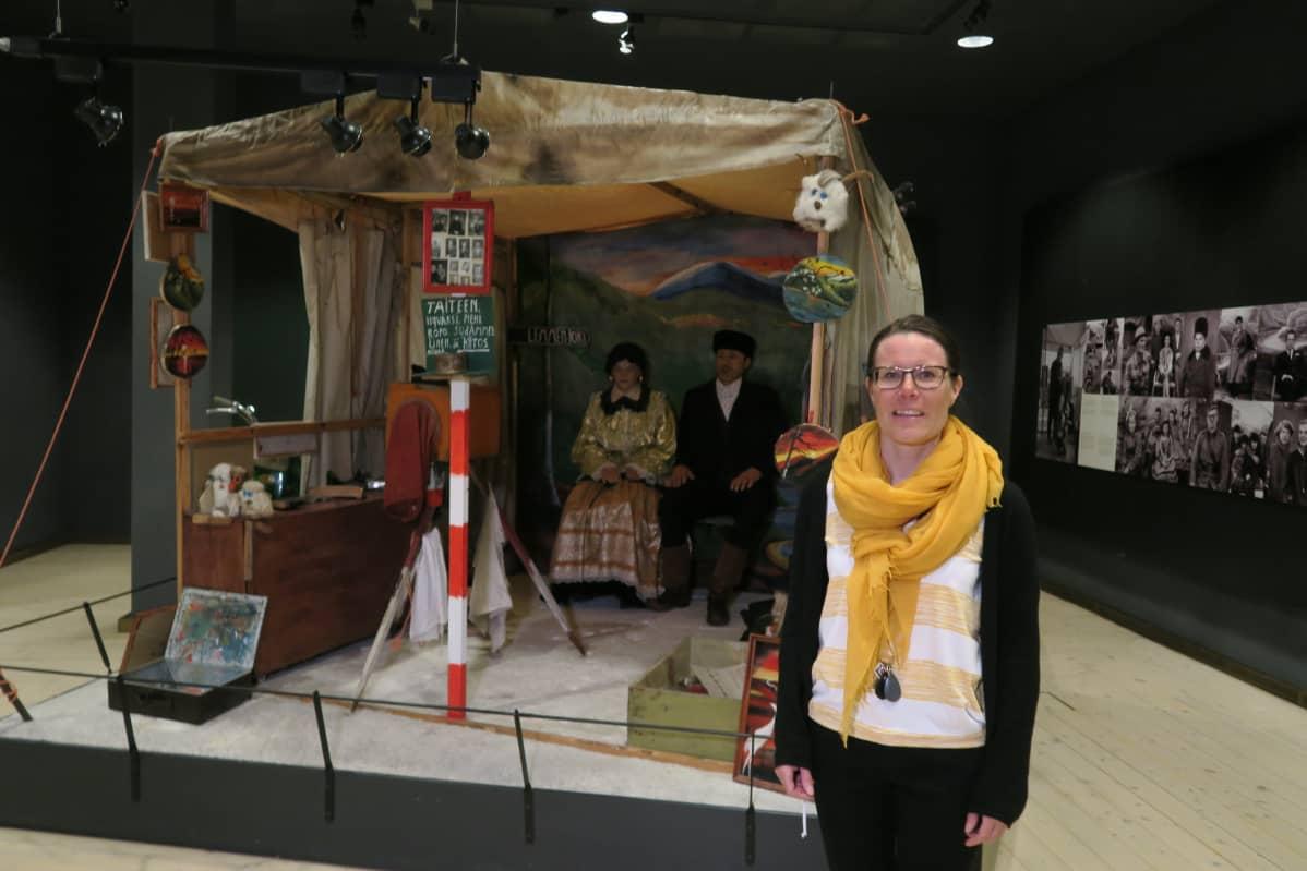 Lapin maakuntamuseon va. museonjohtaja Hanna Kyläniemi perusnäyttelyssä esillä olevan Valto Pernun kuvausteltan edessä.