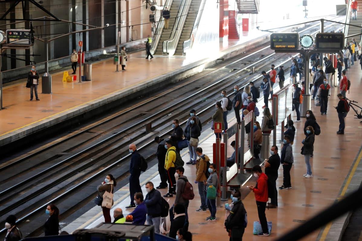 Työmatkalaisia odottamassa junaa Atochan asemalla Madridissa.