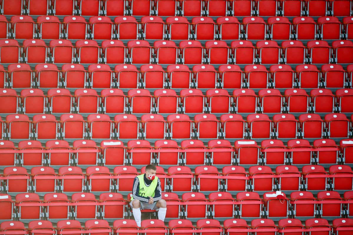 Vaihtopelaaja istuu yksin tyhjässä katsomossa jalkapallo-ottelussa Berliinissä.