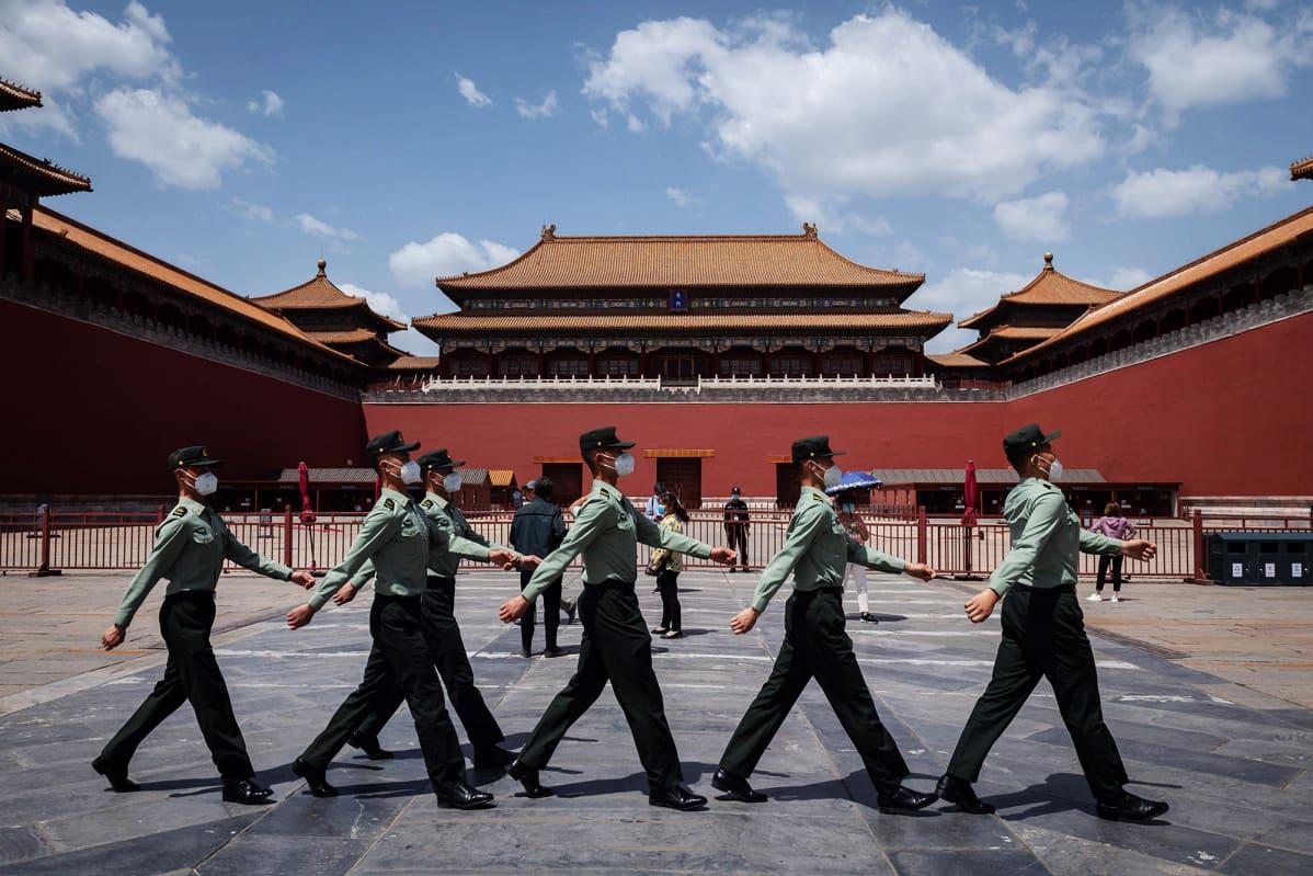 Kuvassa kiinalaiset marssivat hengityssuojia käyttäen Pekingissä.