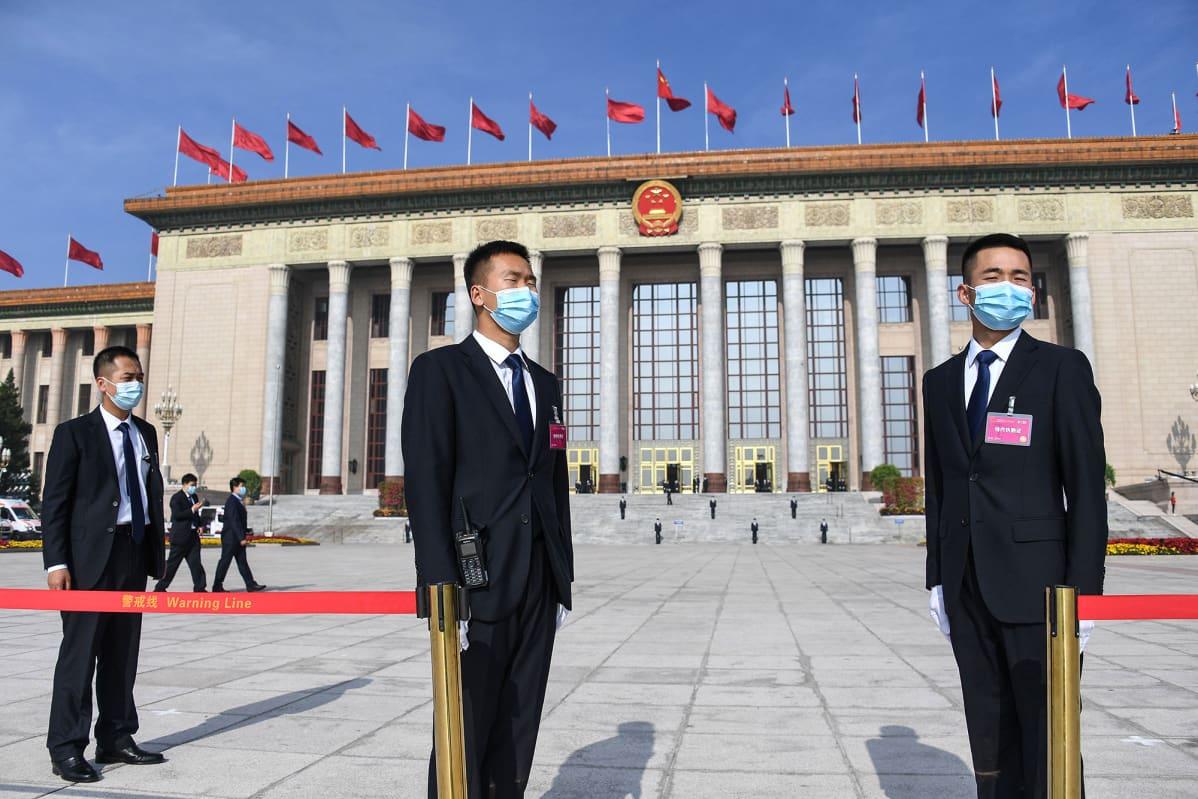 KAsvomaskeihin pukeutuneita turvamiehiä Kiinan kansantasavallan parlamenttitalon edustalla.