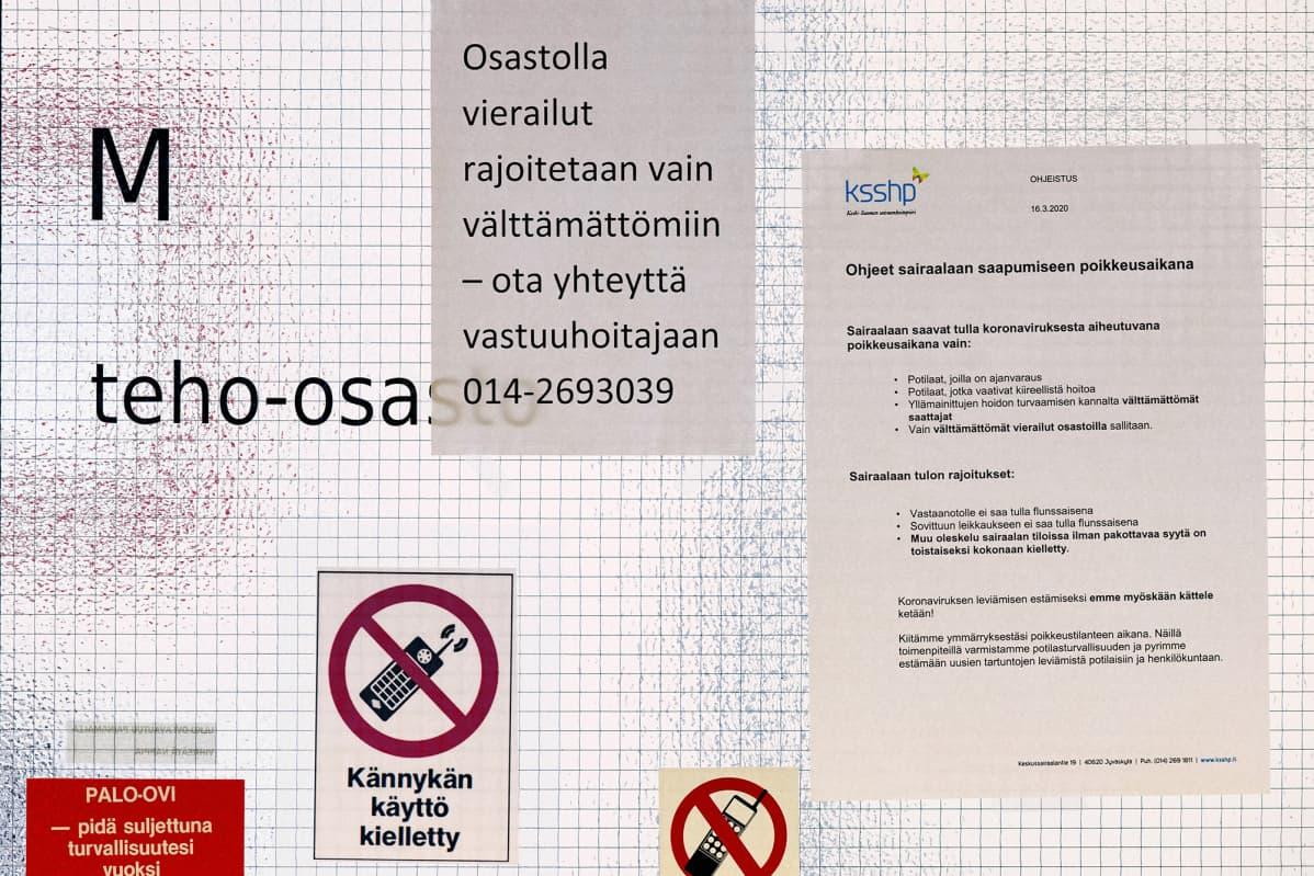 Liikkumisrajoituksia koskevia ilmotuksia teho-osaston ovessa Keski-Suomen keskussairaalassa.
