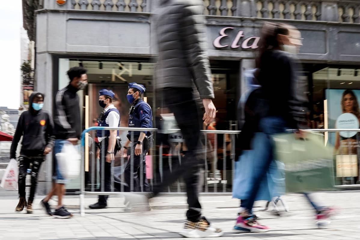 Suojamaskeihin pukeutuneet poliisit partioivat kadulla Brysselissä.
