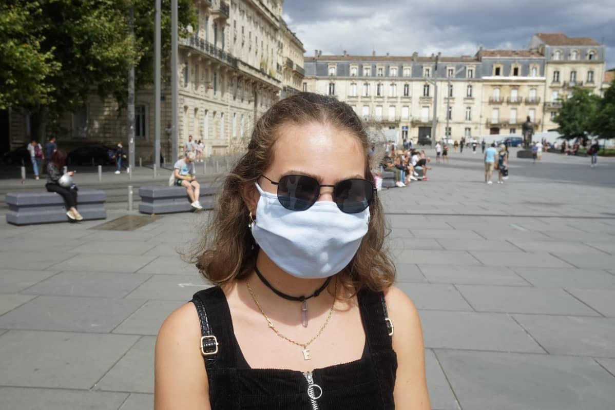 nainen maskissaan torilla