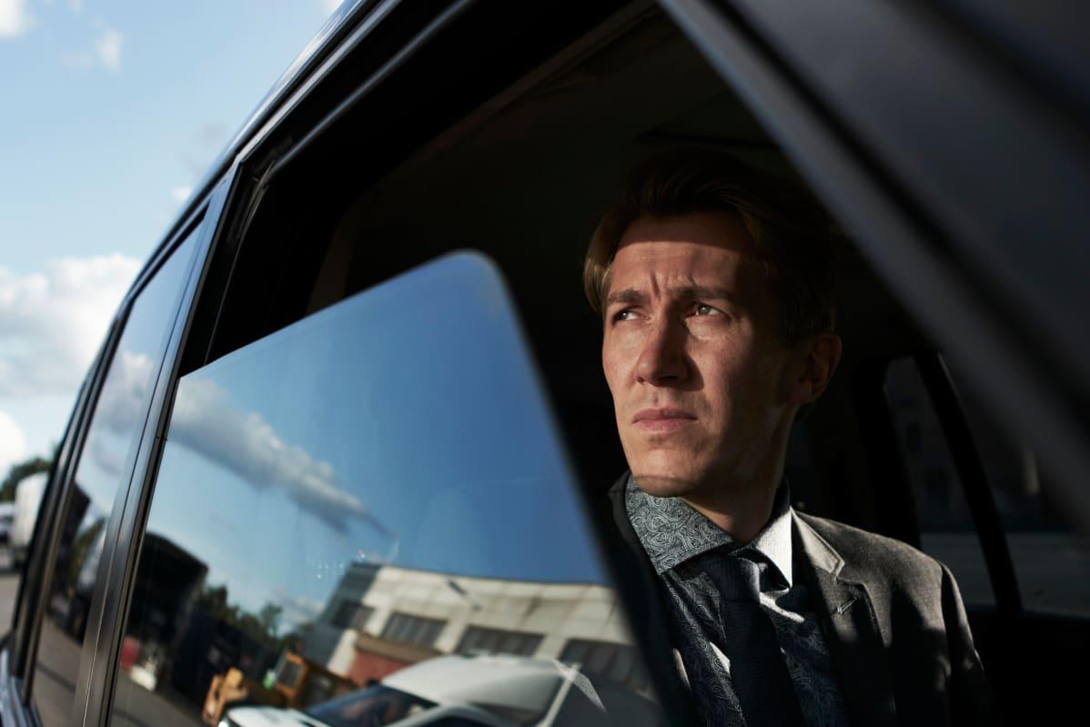 Kuvassa Jussi Vatanen. Hän katsoo auton ikkunasta ulos. Auton ikkunan heijastuksesta näkyy tehdas.