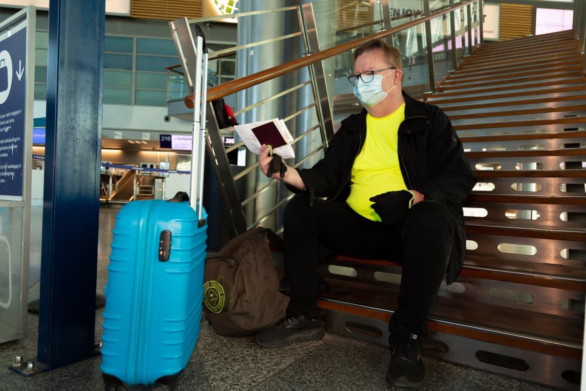 Risto Niemi istuu Helsinki-Vantaan lentoaseman lähtöaulassa rappusilla hengähtämässä ja tarkastamassa matkapapereitaan. Ristolla on keltainen t-paita ja mustat farkkuhousut ja -takki. Vedettävä matkalaukku on kirkkaan sininen.