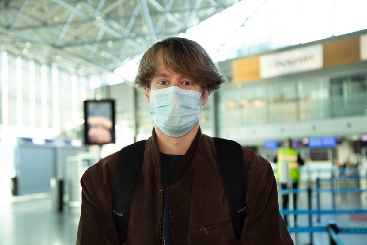 Dylan Pashly Helsinki-Vantaa lentoaseman lähtöaulassa. Dylanilla on ruskea takki ja kasvoilla hengityssuojain.