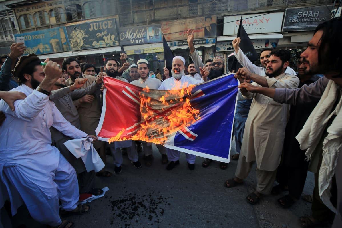 Pakistani people burn a mock of a French flag during a demonstration against French President Macron's comments over Prophet Muhammad caricatures, in Peshawar, Pakisan, 26 October 2020. A group of protestors gathered to protest Macron's comments following the recent beheading of a teacher in France, after he had shown caricatures of the Prophet Muhammad in class. Macron vowed his country would not give up publishing such cartoons. EPA-EFE/ARSHAD ARBAB