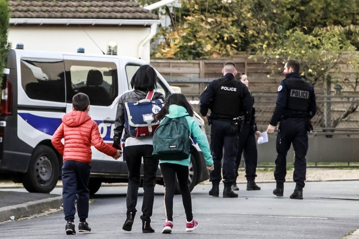 Koululaisia ja poliiseja koulun edessä