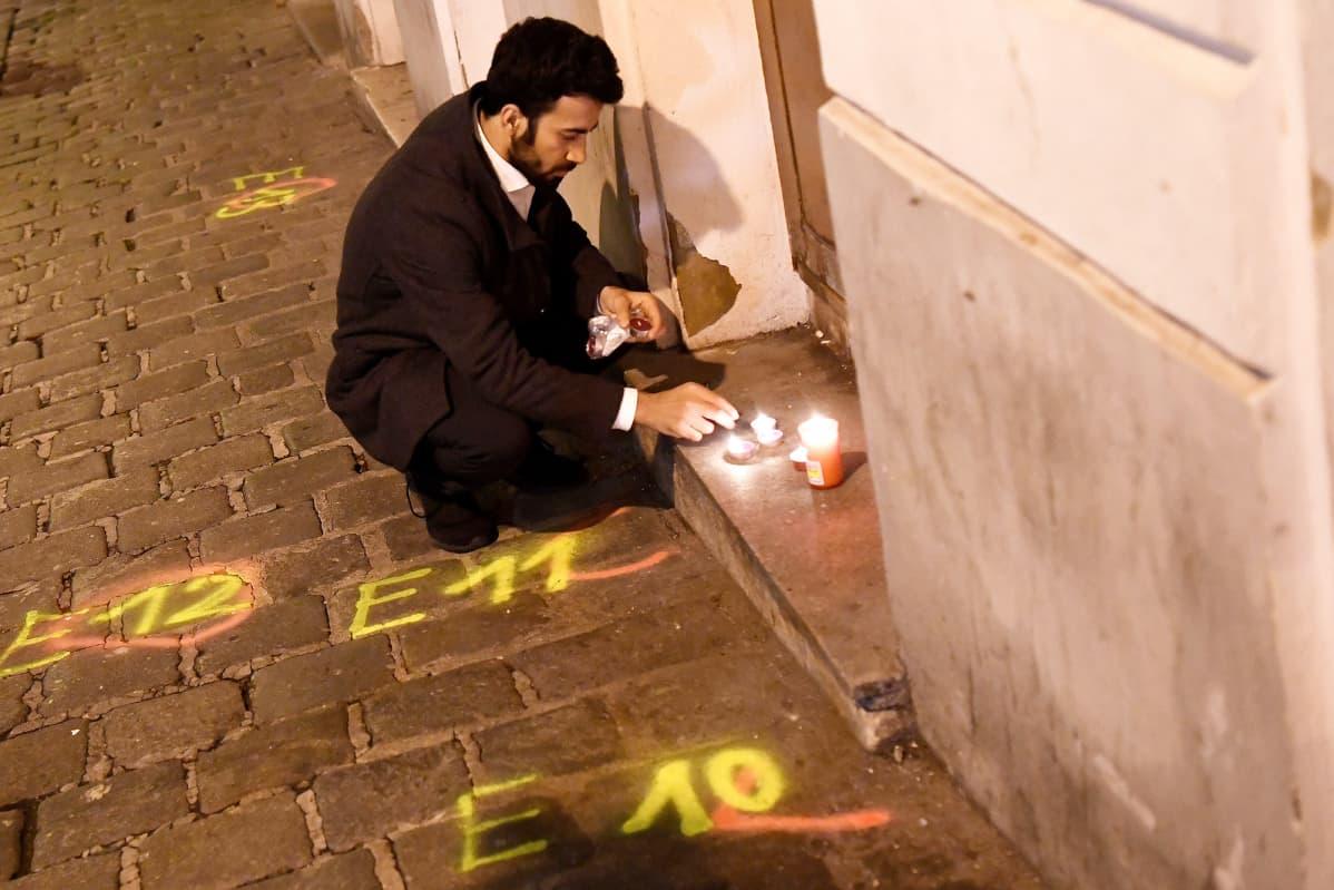 Mies sytytti kynttilän rikospaikalla Wienissä tiistaina.