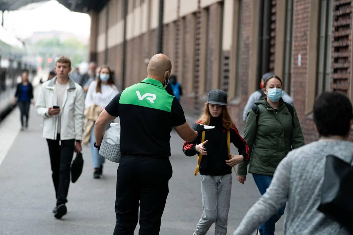 VR:n työntekijä jakaa kasvomaskeja Helsingin päärautatieasemalla.