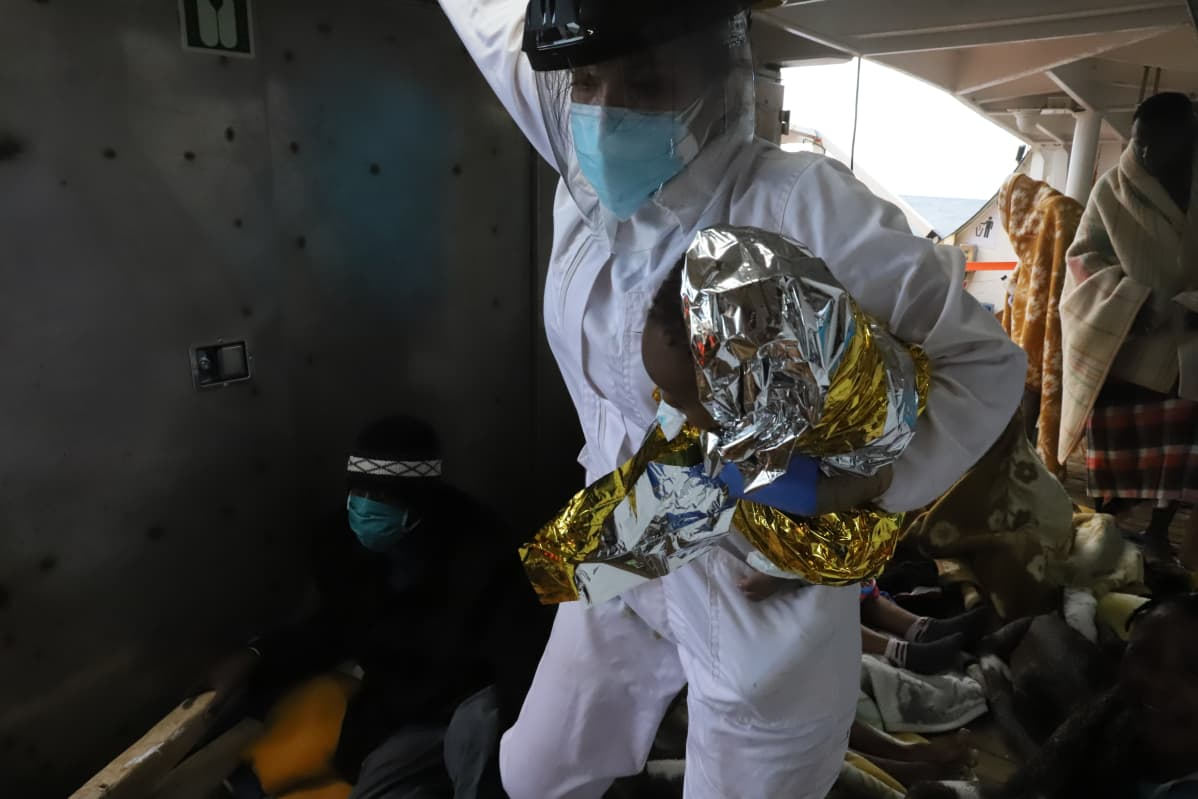 Open Arms -aluksen lääkäri kannattelee merestä nostettua Joseph-vauvaa. Hän ei selvinnyt matkasta.
