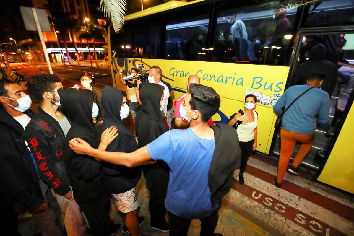 Siirtolaiset jonottavat bussikuljetukseen Las Palmasissa.