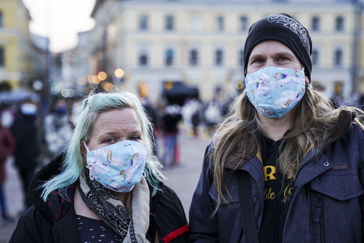 Sini Kipinä ja Antti Kotinurmi poseerasivat maskit kasvoillaan Senaatintorilla.