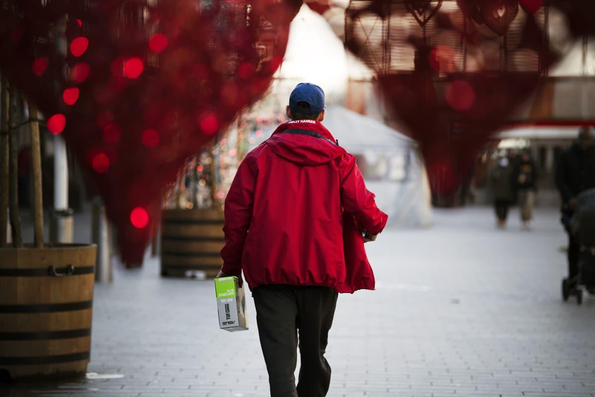 Mies kävelee joulukoristellulla ostoskeskuksen edustalla.