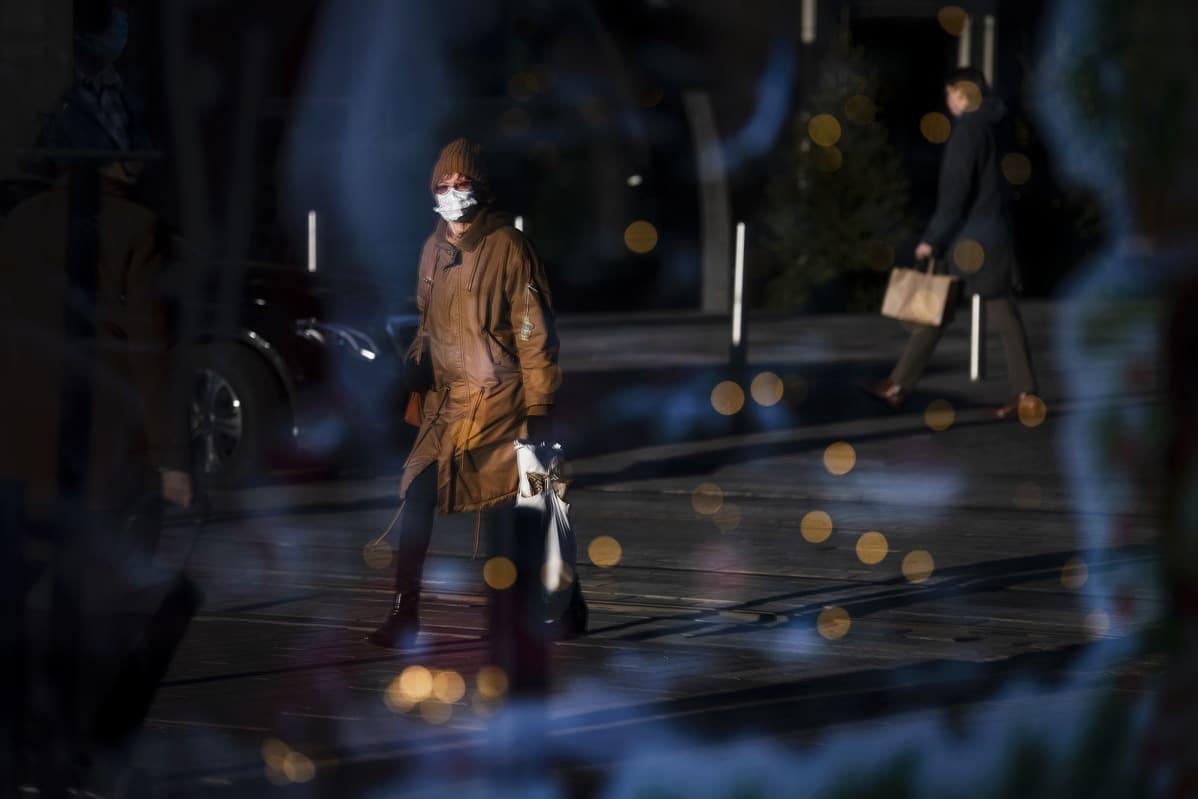 Kasvomaskiin pukeutunut nainen kävelee kadulla.
