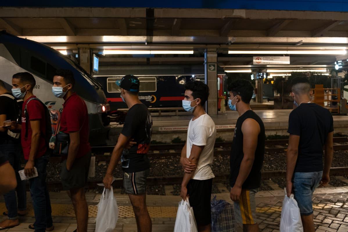 miehiä jonottamassa juna-asemalla
