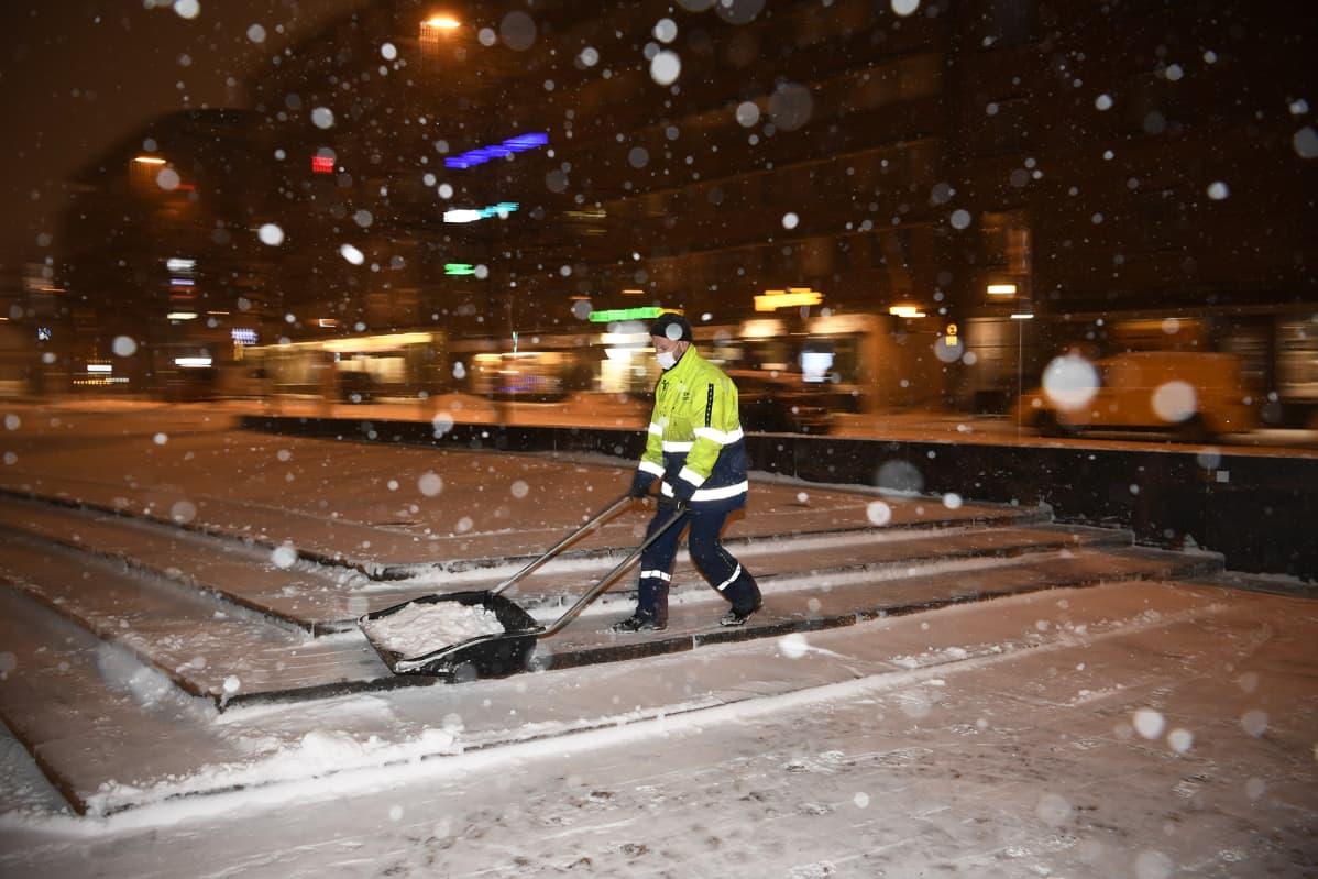 Mies kolaa lunta Kampintorilla.