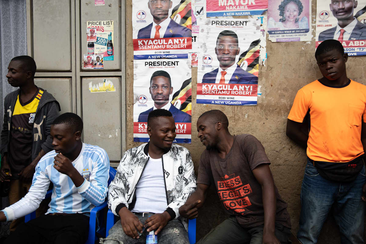 Alan Mugisa istuu ystäviensä kanssa Kamwokyan slummialueella, missä Bobi WIne kasvoi.