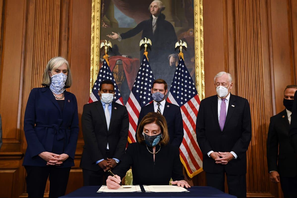 Nancy Pelosi allekirjoittaa virkasyyteasiakirjan.
