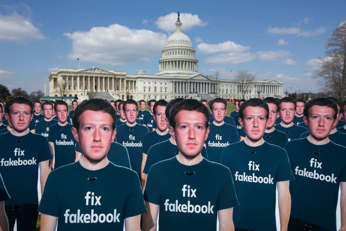 """Mark Zuckerbergin pahvihahmojen t-paidoissa lukee teksti """"fix fakebook"""". Yhdysvaltain kongressirakennus taustalla."""