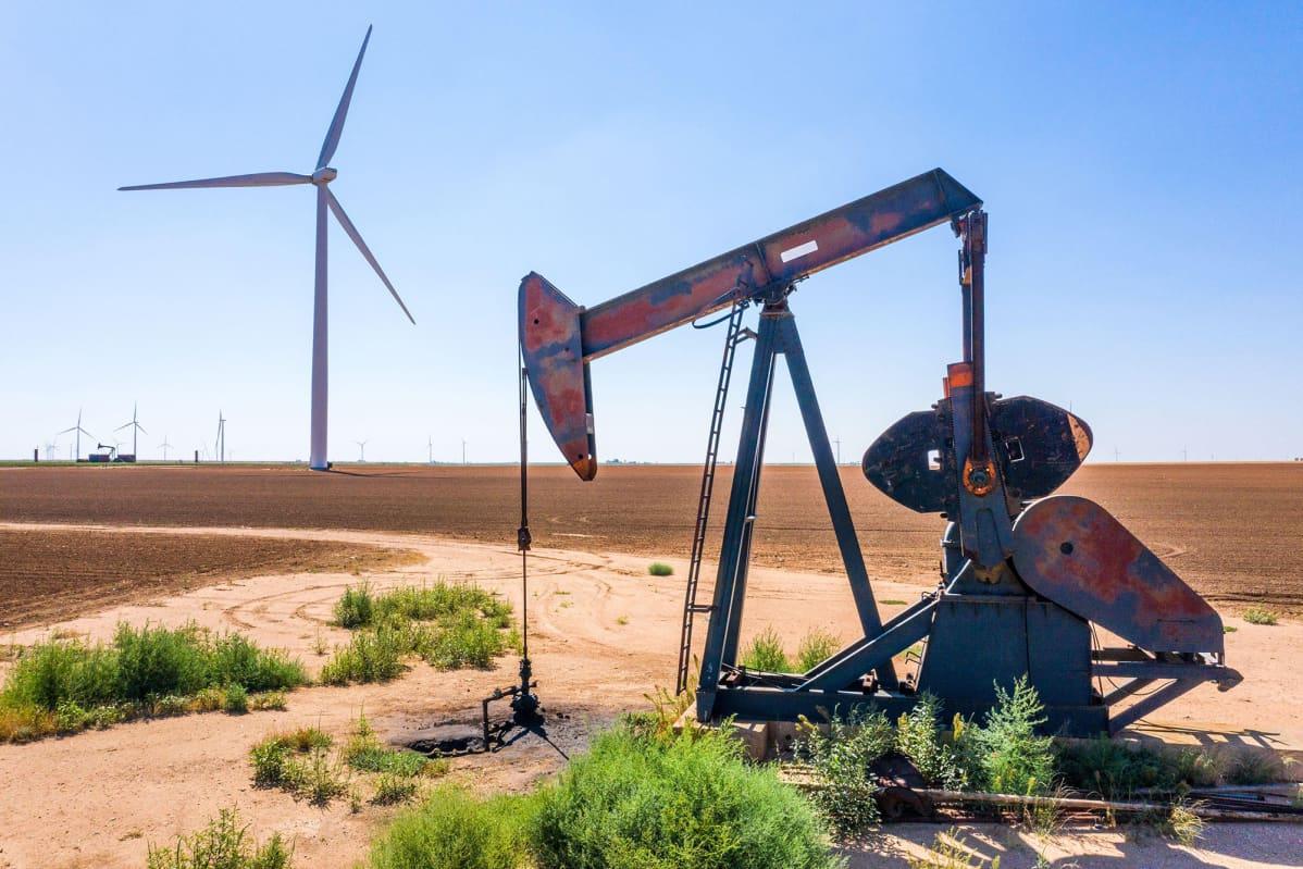 Maisemakuva öljynporaustornista ja tuulimyllystä Teksasissa.
