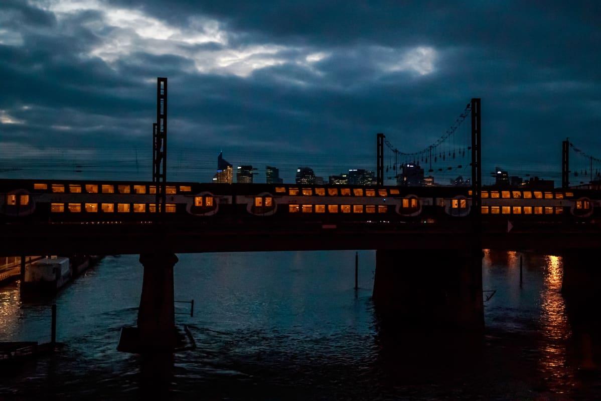 Paikallisjuna valistuna sillalla yöllä.