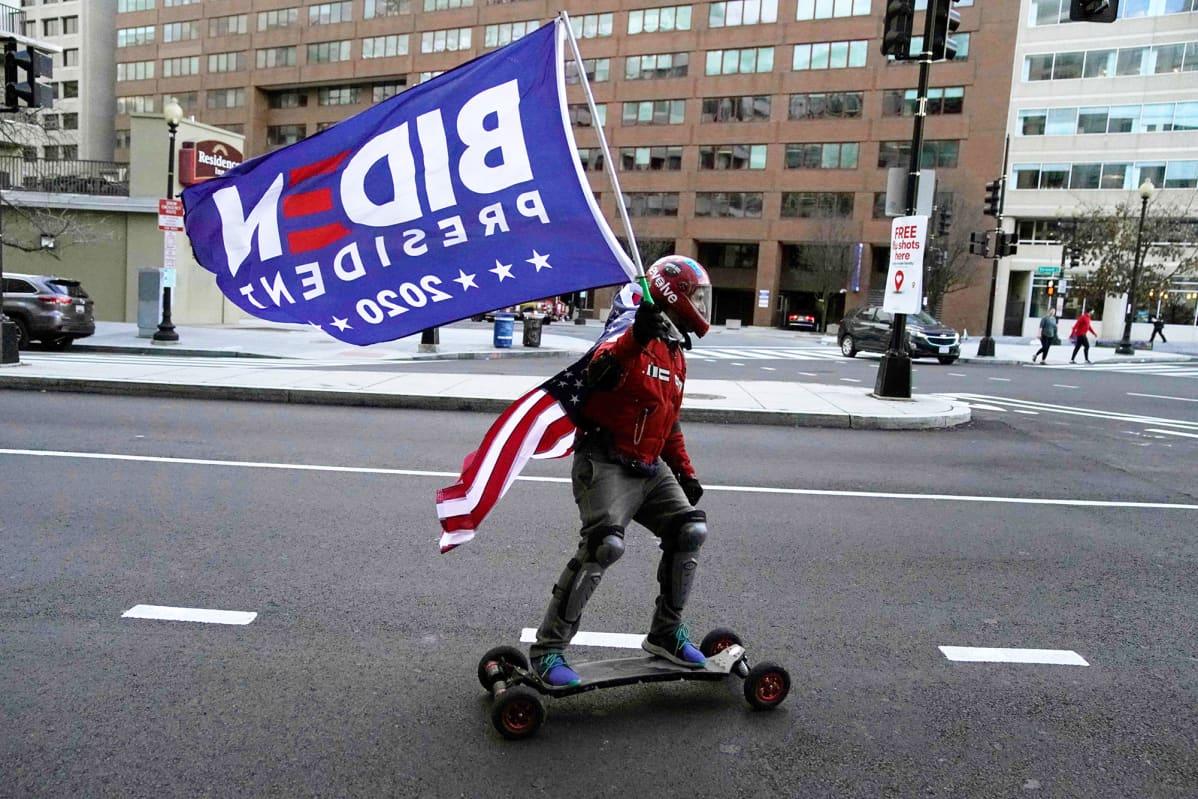 Rullalautailija  liehuttaa Biden-lippua Washingtonissa