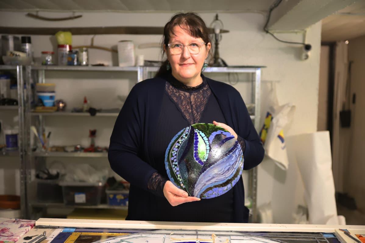 Lasiartesaani Minna Enqvist esittelemässä lasiteostaan kodissaan Kotkassa.