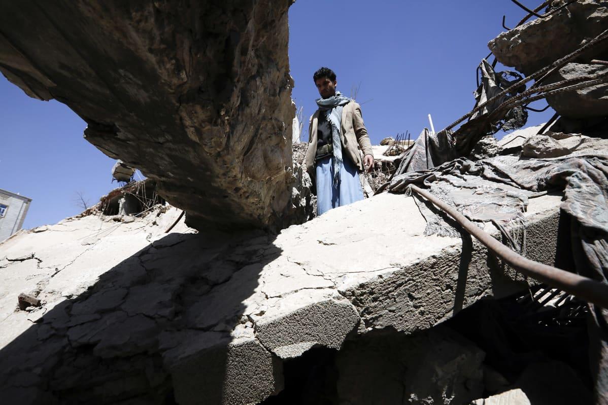 Jemeniläinen tarkastaa pommitetun rakennuksen jäänteitä.