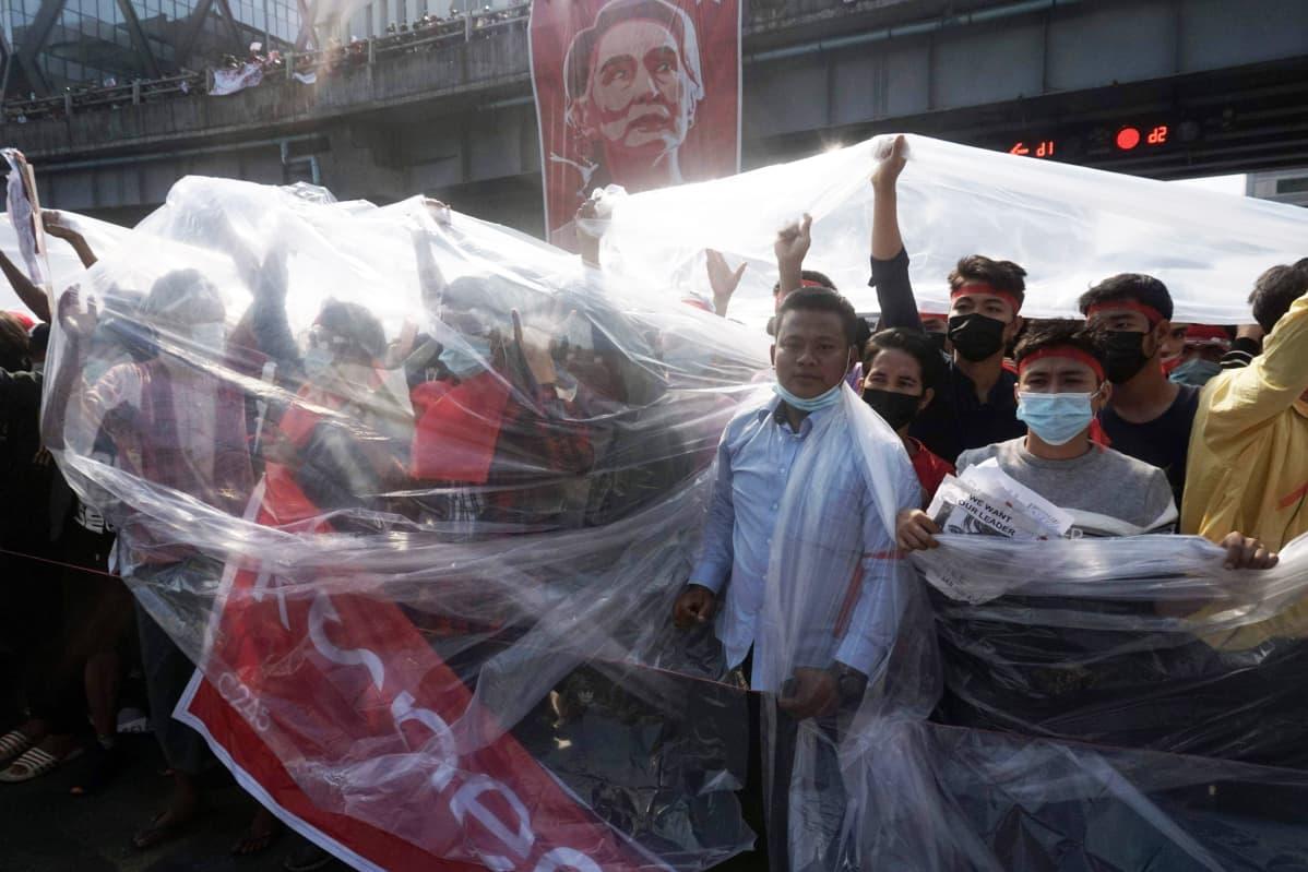 Mielenosoittajat suojautuvat muoveilla Yangonissa.