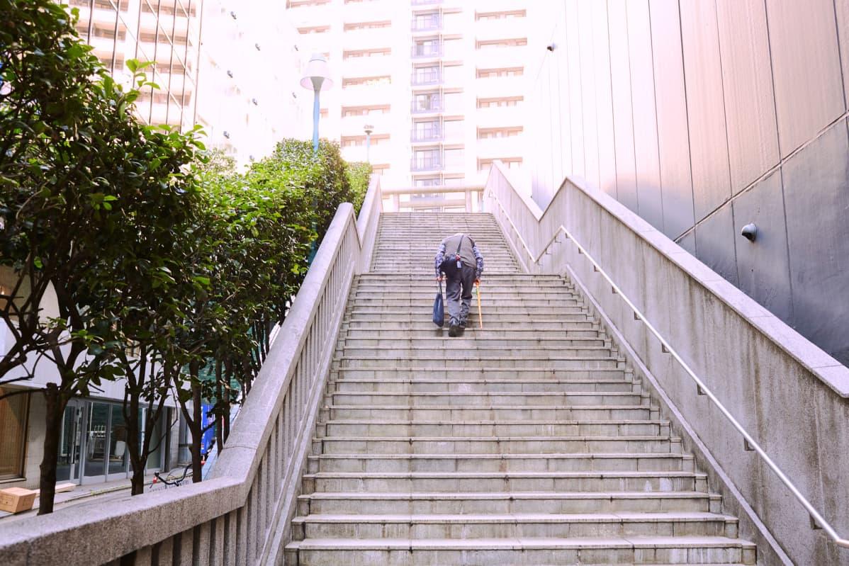 Vanhus kävelee ylös rappusia Shibuyassa, Tokiossa.
